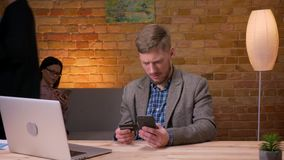 Lanzamiento del primer del hombre de negocios adulto que hace compras en línea en el teléfono delante del ordenador portátil dent almacen de video