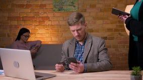 Lanzamiento del primer del hombre de negocios adulto que hace compras en línea en el teléfono dentro en la oficina El usar femeni metrajes