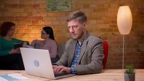 Lanzamiento del primer del hombre de negocios adulto que mecanografía en el ordenador portátil que mira la cámara y que sonríe de almacen de video