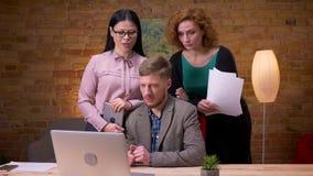 Lanzamiento del primer del hombre de negocios adulto que trabaja en el ordenador portátil dentro en la oficina Tres empleados que almacen de metraje de vídeo