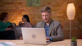 Lanzamiento del primer del hombre de negocios adulto que usa el ordenador portátil que mira la cámara y que sonríe dentro en la o metrajes