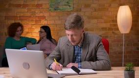 Lanzamiento del primer del hombre de negocios adulto que usa el ordenador portátil que toma notas dentro en la oficina Empleado d almacen de video