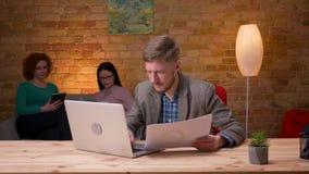 Lanzamiento del primer del hombre de negocios adulto que usa el ordenador portátil y analizando gráficos dentro en la oficina Emp metrajes