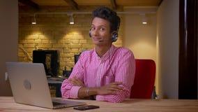 Lanzamiento del primer del hombre de negocios joven indio en los auriculares que miran la cámara que sonríe happilly usando el or metrajes