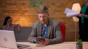 Lanzamiento del primer del hombre de negocios joven que usa la tableta delante del ordenador portátil y mostrando la pantalla ver metrajes