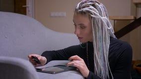 Lanzamiento del primer del inconformista caucásico atractivo joven femenino con los dreadlocks que hacen compras en línea en la t almacen de metraje de vídeo