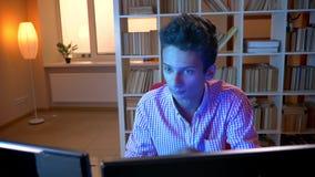 Lanzamiento del primer del var?n atractivo indio joven que juega a los videojuegos en el ordenador dentro en el apartamento acoge almacen de metraje de vídeo