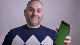 Lanzamiento del primer del varón caucásico envejecido medio que hojea en el ordenador portátil y que muestra la pantalla verde de metrajes