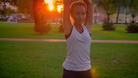 Lanzamiento del primer del varón joven y del acroyoga de entrenamiento femenino en el parque al aire libre Hombre que miente en l metrajes