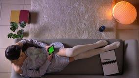 Lanzamiento del top del primer del adolescente femenino atractivo joven que hojea un app en el teléfono con la pantalla verde de  almacen de metraje de vídeo