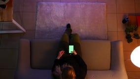 Lanzamiento del top del primer del adolescente femenino bonito que ve la TV usando el teléfono con la pantalla verde mientras que