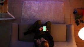 Lanzamiento del top del primer del adolescente femenino bonito que ve la TV usando el tel?fono con la pantalla verde mientras que