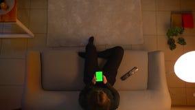 Lanzamiento del top del primer de la hembra bonita joven usando el tel?fono con la pantalla verde mientras que ve la TV y si?ntas almacen de metraje de vídeo