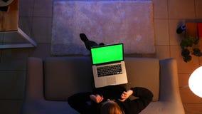Lanzamiento del top del primer de la hembra bonita usando el ordenador portátil mientras que se sienta en el sofá dentro en un ap almacen de metraje de vídeo
