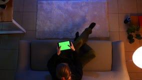 Lanzamiento del top del primer de la hembra bonita usando la tableta con los videojuegos verdes de la pantalla y el jugar mientra almacen de video