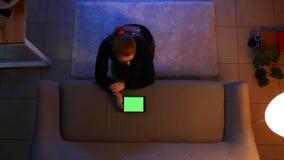 Lanzamiento del top del primer de la hembra bonita usando la tableta con la pantalla verde y la mensajer?a mientras que se sienta metrajes