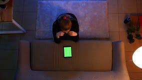 Lanzamiento del top del primer de la hembra bonita usando la tableta y hacer compras en línea mientras que se sienta en la alfomb metrajes