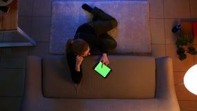 Lanzamiento del top del primer de la hembra bonita usando la tableta y hacer compras en línea mientras que se sienta en el piso d metrajes