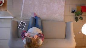 Lanzamiento del top del primer de la hembra embarazada joven que discute una imagen del rayo x de su bebé que habla en el teléf almacen de video