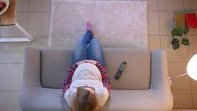 Lanzamiento del top del primer de la hembra embarazada joven que ve la TV usando el rato teledirigido que se sienta en la tenenci almacen de metraje de vídeo