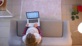 Lanzamiento del top del primer de la hembra embarazada joven usando el ordenador portátil mientras que se sienta en el sofá den almacen de metraje de vídeo