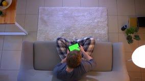 Lanzamiento del top del primer de la mensajer?a masculina ocasional vestida joven en la tableta con la pantalla verde de la croma metrajes