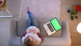 Lanzamiento del top del primer de la ojeada femenina embarazada joven en el ordenador portátil con la pantalla verde de la croma almacen de metraje de vídeo