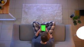 Lanzamiento del top del primer de la ojeada masculina joven en la tableta con la pantalla verde de la croma mientras que se sient