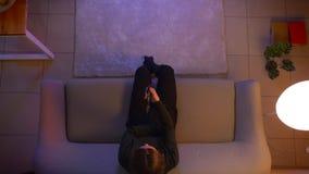 Lanzamiento del top del primer de la TV de observaci?n femenina bonita joven que camina y que se sienta en el sof? dentro en el h almacen de video