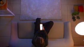 Lanzamiento del top del primer de la TV de observaci?n femenina bonita joven que se sienta en el sof? usando un app en el tel?fon almacen de metraje de vídeo