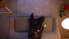 Lanzamiento del top del primer de la TV de observación femenina bonita joven que se sienta en el sofá usando un app en el teléfon almacen de metraje de vídeo