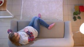Lanzamiento del top del primer de la TV de observación femenina embarazada joven mientras que se sienta en el sofá y suavemente almacen de video