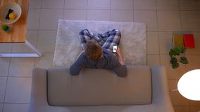Lanzamiento del top del primer de la TV de observaci?n masculina joven que se sienta en el piso y que usa un app en el tel?fono c almacen de video