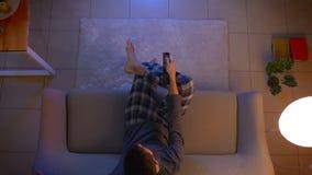 Lanzamiento del top del primer de la TV de observaci?n masculina joven que se sienta en el sof? dentro en el hogar acogedor con l metrajes