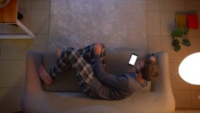 Lanzamiento del top del primer de la TV de observaci?n masculina joven y de usar un app en el tel?fono como mentira teledirigida  almacen de metraje de vídeo