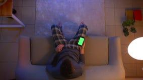 Lanzamiento del top del primer de la TV de observación masculina joven y de usar un app en el teléfono con la pantalla verde como metrajes