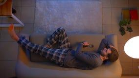 Lanzamiento del top del primer de la TV de observaci?n masculina linda joven que miente en el sof? dentro en el hogar acogedor co almacen de metraje de vídeo