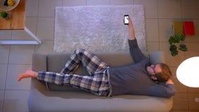 Lanzamiento del top del primer de la TV de observación masculina ocasional vestida joven que miente en el sofá y que usa un app e metrajes