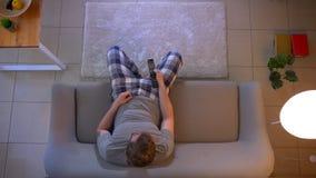 Lanzamiento del top del primer de la TV de observación masculina ocasional vestida joven que se sienta en el sofá y que usa el te