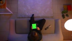 Lanzamiento del top del primer de la web femenina bonita joven de la ojeada en la tableta con la pantalla verde que ve la TV y qu almacen de metraje de vídeo