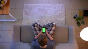 Lanzamiento del top del primer de mandar un SMS masculino ocasional vestido joven en el teléfono con la pantalla verde mientras q