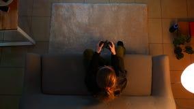 Lanzamiento del top del primer de videojuegos que juegan bastante femeninos mientras que se sienta en el sofá dentro en un aparta
