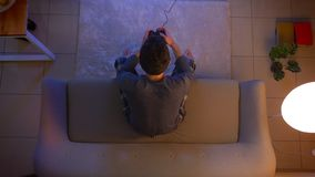 Lanzamiento del top del primer de videojuegos que juegan masculinos jovenes en la TV usando la videoconsola que se sienta en el s