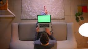 Lanzamiento del top del primer del establecimiento de una red del hombre joven en el ordenador portátil con la pantalla verde mie