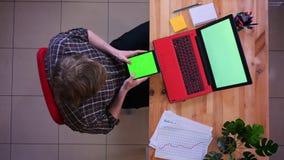 Lanzamiento del top del primer del hombre de negocios caucásico joven que manda un SMS en la tableta con la pantalla verde de la  almacen de video