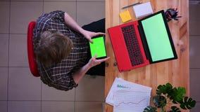 Lanzamiento del top del primer del hombre de negocios caucásico joven que manda un SMS en la tableta con la pantalla verde delant metrajes