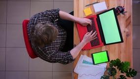 Lanzamiento del top del primer del hombre de negocios caucásico joven que mecanografía en el ordenador portátil con la tableta co almacen de video