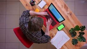 Lanzamiento del top del primer del hombre de negocios caucásico joven que mecanografía en el ordenador portátil con un teléfono e metrajes