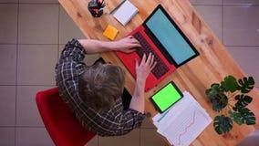 Lanzamiento del top del primer del hombre de negocios caucásico joven que mecanografía en el ordenador portátil con una tableta c metrajes