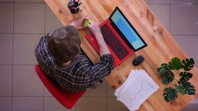 Lanzamiento del top del primer del hombre de negocios caucásico joven que mecanografía en el ordenador portátil en el escritorio  almacen de video